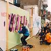 F2512<br /> Graffitikunstenaars aan de slag op de bouwschutting tussen de Hema en de Etos aan de Hoofdstraat. Foto: 2003.