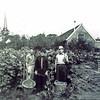 F0169 <br /> Foto uit begin jaren zestig. Links Klaas Oudshoorn, in het midden J. Hogewoning sr. en rechts Jo Oudshoorn. De groentetuin werd gehuurd van Stelma. De tuin lag achter de Boschlaan waar nu (2016) het Boschplein is. De schuur rechts was van de vroegere bakker Stelma, die gehuwd was met een zuster van Vlasveld (woonde vooraan op de Kerklaan). De schuur was ook  van een andere broer die vlakbij de Bijweglaan woonde. Op de achtergrond de toren van de Ned.-herv. kerk (Dorpskerk). Op deze locatie is nu de Passage. Foto:  ca. 1962.