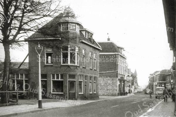 F0538 <br /> Hoofdstraat, centrum. De kapperszaak van Jan de Jong achter de lantaarnpaal staat leeg; het pand is in 1959 gesloopt. De kleine huisjes, die daarnaast stonden waren in 1957 al afgebroken. De winkel van De Gruyter 10%, voorheen de wijn- en sigarenwinkel van Francken, staat er nog. Nu (2016)  zijn hier het dorpsplein en de Hortuslaan. Foto: 1959.