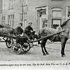 F0548 <br /> Arie Vos met zijn knecht C. v.d. Pijl op de bok van de kolenwagen. De foto is genomen op de hoek van de Bijdorpstraat (links) en de Hoofdstraat (rechts) bij de bakkerswinkel van H.C. Stelma. Op de achtergrond is de schoorsteenpijp van de bakkerij te zien. Foto: jaren '30.