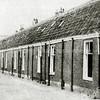 F2201<br /> De voormalige woningen aan de Hoekstraat, afgebroken in 1975. We kijken in westelijke richting, richting Hoofdstraat. Het lange blok huizen zijn v.l.n.r. de nummers 11 t/m 27. Het huis aan het eind, dat er dwars op staat, is nr. 3. De andere zijde van de Hoekstraat is afgebroken in 1972.