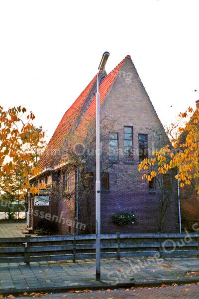 F0194 <br /> Het kerkgebouw van de Ned. Prot. Bond, Julianalaan 17. Het gebouw heeft een hoog, spits toelopend dak en de ingang is aan de zijkant. Voor zover bekend is er aan het gebouw uit de jaren dertig weinig veranderd. De ruimte eromheen is zeer beperkt en leent zich niet voor enige uitbreiding. Gesloopt begin deze eeuw. Op deze plek staan nu (2016) een twee-onder-een-kapwoning. Foto: 1996.