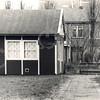 F4607<br /> Rechts van het voormalige kostershuis op Parklaan 1 liep een pad naar dit houten gebouw: 't Velthuys. Het was een verenigingsgebouw, eind jaren '90 gebouwd voor de scoutingsvereniging Scojesa. Deze vereniging was in 1959 opgericht, op initiatief van kapelaan J.G.M. Velthuyse, die van 1956  tot 1962 kapelaan was in de St. Pancratiusparochie. In 1973 werd het gebouwtje door de parochie voor één gulden verkocht aan de vereniging. Eind 2001 werd het gesloopt, vanwege uitbreiding van het kerkhof. Scojesa ging naar een nieuw onderkomen achter zwembad Wasbeek.<br /> Op de achtergrond zien we de achterzijde van huizen die op Pancraszicht staan.