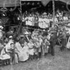 F0720c <br /> Het eeuwfeest 1813-1913, het onafhankelijkheidsfeest. De uitvoering van de Kleppermarsch op 17 september 1913 op het feestterrein op de overplaats van Rusthoff. Er deden zo'n 150 schoolkinderen aan mee en ze brachten zo een hommage aan de klepperman (klapwaker of nachtwacht), die een eeuw daarvoor nog 's nachts de wacht hield in het dorp en ieder uur zijn ronde deed. Op het podium de kinderen: links de jongens en rechts de meisjes. Links onder het baldakijn de muzikanten van het Chr. Fanfarekorps Crescendo naast hun vaandel. De man rechts met de witte hoed is Joannes Bernardus IJsselmuiden. Foto: 1913.