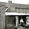 F0029 <br /> Het bollenbedrijf van Klaas Oudshoorn, achterin de Zuiderstraat. Let op de letters K.O. op de deuren en manden. De staande man is de Duitser Harold Olie, een vriend van Arie Oudshoorn. Foto: ca. 1930. F0027/28/30