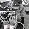 F3728<br /> Van gekopte narcissen werden slingers gemaakt die door veel bollenstrekers langs de weg verkocht werden. Dit is Roel Roodenburg met Miriam Meijer in zijn bloemenstand aan de Hoofdstraat vlakbij de Uiver.
