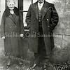 F0623 <br /> Willem Zijerveld en Lijsje Zijerveld-Vellekoop achter hun huis aan de Hoofdstraat. Willem was timmerman, begrafenisondernemer van de eerste Sassenheimse begrafenisvereniging  De Laatste Eer en hij was bode voor het ziekenfonds. Zijn vrouw Lijsje had een kruidenierswinkel, eerst in de Zuiderstraat op nr. 5 en later na verhuizing aan de Hoofdstraat nr. 103. Foto: ca. 1925.
