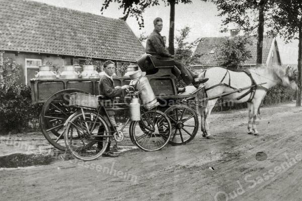 F0550 <br /> Op de Menneweg de melkbrik met Klaas Breedijk op de bok en het paard Corrie ervóór. Bij de transportfiets met de melkbus staat de ca. 14-jarige Kees Breedijk. Op de achtergrond het rijtje huizen dat 'Het Wespennest' genoemd werd, en de boerderij van Kees v.d. Ploeg. Foto: ca. 1927.