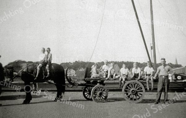 F1053 <br /> De Oosthaven ter hoogte van waar nu de brug in de Parklaan is. Er wordt kisthout vervoerd naar de werkplaats. De staande persoon links is waarschijnlijk J. Nicola. Rechts staat Dirk Staring. De kinderen mochten meerijden als de wagen leeg terugging. Op de achtergrond zien we de bomen van Park Rusthoff en de torenspits van de St. Pancratiuskerk. Foto: 1936.