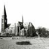 F0463 <br /> De St. Pancratiuskerk, gezien vanaf het terrein waar nu het appartementencomplex Parkstate staat, met zicht op de begraafplaats. De kerk is in twee delen gebouwd. In 1913 werden het priesterkoor, het dwarsschip en de toren gebouwd naar een ontwerp van architect J. Tonnaer. In 1928/29 werden het middenschip en een nieuwe, de huidige, toren gebouwd door aannemer W. de Vrede uit Noordwijk, bouwsom f 149.300,-. De kerk werd op 2 oktober 1929 ingewijd. Aan de bouw is de naam van pastoor J.H.A. Thus voorgoed verbonden. Deze pastoor diende de parochie van 1911 tot 1932.