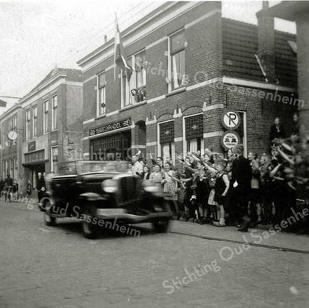 F0362b <br /> De intocht van de Canadezen met zwaaiende mensen tijdens de bevrijding in mei 1945. Foto genomen in de Hoofdstraat. Rechts de winkel van smederij Bruijnen en onder de klok de snoepwinkel van Jamin. Foto: 1945.