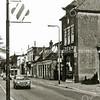 F1656 <br /> Het centrum van Sassenheim, gezien naar het noorden. Rechts de damesmodezaak van P.C. Melman, de lage huizen van C. Melman en van de fam. Stelma; de bakkerswinkel van Van der Horst en de fruitwinkel van Faas. Het huis van J. Oudshoorn, Klaas den Boer en de winkel van C. Verlint zijn hier al gesloopt en vervangen door een nieuw pand van Albert Heijn. Links 't Bruine Paard. Foto: 1976.