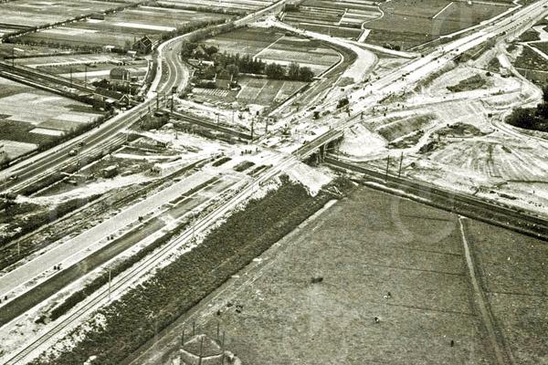 F4438<br /> In de jaren dertig werd een begin gemaakt met de aanleg van snelwegen in Nederland. Nummer 4 in de rij was die tussen Amsterdam en Den Haag. In 1938 was het gedeelte tussen Amsterdam en Sassenheim gereed. Van het punt waar de snelweg de reeds bestaande Rijksstraatweg/Haarlemmerstraatweg  doorkruiste, is helaas geen luchtopname. Maar de opname hierboven geeft een mooi beeld van de toenmalige werkzaamheden. Merk op dat de trambaan al verlegd is: die komt linksonder vanaf de Haarlemmerstraatweg in Oegstgeest en wordt dan langs de oostzijde van de snelweg geleid – over de 'vluchtstrook'. Dan gaat de trambaan over de spoorlijn heen en met de afrit mee omlaag. Vervolgens het Klinkenbergerviaduct onderdoor (zie foto pag. 22) om daarna weer aan te sluiten op de bestaande baan. De Rijksweg 4, zoals de snelweg aanvankelijk heette, werd geopend op 25 juni 1938. Een jaar later was het gedeelte tot Oegstgeest klaar, vanaf het viaduct over de spoorlijn.