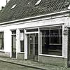 F0172 <br /> Het woonhuis en de kruidenierswinkel van Gerrit van Egmond aan de Kerklaan. Zijn vrouw hielp in de winkel en Van Egmond zelf was poelier en ventte met ijs. Uiterst rechts is een reclamebord te zien. Ook duidt het bordje 'Verlof B' op de verkoop van frisdranken. Na de dood van hun vader zetten de zoons Theo en Kees het poelierschap nog jaren voort. De winkel werd opgedoekt. Kees was ongehuwd en kon de zaak niet alleen voortzetten. In het jaar 1975 is de hele buurt gesloopt om plaats te maken voor het Boschplein, Albert Heijn en de bibliotheek.  Foto: 1975.