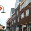 F2023<br /> De Havenpoort, gelegen tussen het Voorhavenkwartier en de Hoofdstraat. Het witte huis in de verte is het voormalige café Van Hage. Links: 'Moeders Eethuis'. Aan de rechterkant winkels met bovengelegen appartementen. Foto: 2009.