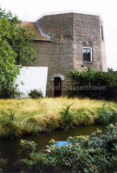 F0207 <br /> De molenstomp van de vroegere molen 'De Nijverheid' van Speelman. In 1989 verdween de laatste huurder Polyvroom, die daar zijn technische dienst had gevestigd. Het was de bedoeling de grond voor huizenbouw  te bestemmen, maar in 1990 werd de Stichting Oud Sassenheim opgericht en de stomp werd dankzij de inspanningen van de SOS behouden. Op de foto is de aanbouw nog intact maar die verdween in 1994. Zie ook De geschiedenis van de Molen van Sassenheim door Pascal van der Elst. Foto 1990..