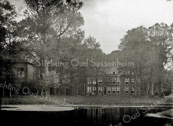 F0620 <br /> Huize Rusthoff te Sassenheim. Deze foto is genomen tussen 1902 en 1916 vanaf de Buitenbeek (latere Charbonlaan). Het huidige park ligt achter het huis.Tussen de bomen links is de achterzijde van het in 1902 gebouwde postkantoor te zien. De kinderen vóór het huis staan op de Hoofdstraat. Foto: begin 20ste eeuw.