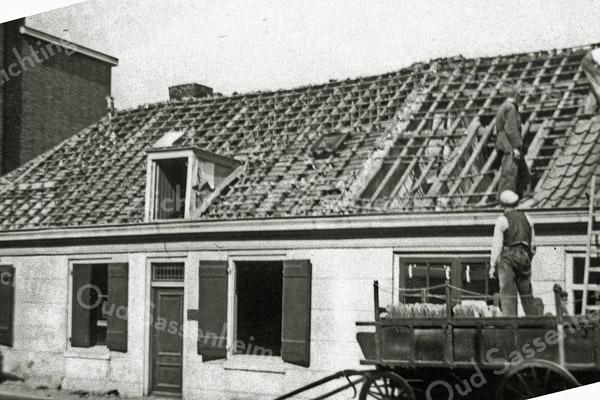 F1057 <br /> De sloop van het oude huis van Vogelaar, Hoofdstraat 209, ten behoeve van nieuwbouw. De dakpannen worden voorzichtig verwijderd voor hergebruik. Nu (2016) is hier Intertoys gevestigd. Foto: 1937.