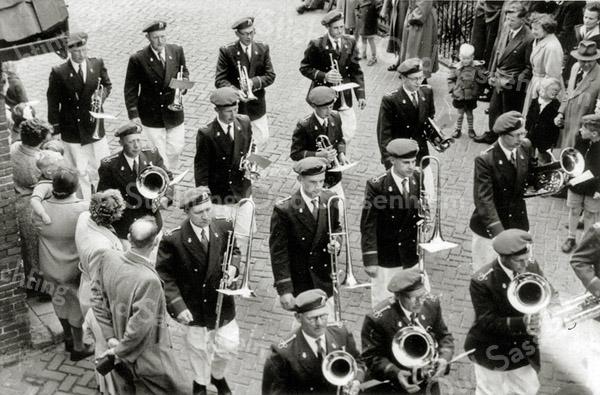 F0990 <br /> Nog een foto van Crescendo in uniform. Nu eens niet de voorzijde van het korps, maar de achterzijde. Van voor naar achter en van links naar rechts ziet u: 1e rij Teun van Leeuwen (sr.), Peet Staring en Ab Helmus (sr.). 2e rij Cees van der Heiden (sr.), Piet Dijkstra, Arie Duijm en Guurt van der Meer. 3de rij Jan Geerling, Piet Bloemendaal, Aad Vos en Henk van der Heiden. 4de rij Joop van der Meer, Fok Moolenaar, Rinus Moolenaar en Gerrit van der Heiden. Foto: 1955.