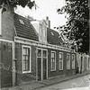 F0858 <br /> Op het tegenwoordige Boschplein, rechts van de bibliotheek stond deze smederij van Ph. Bakker. In de schuur uiterst links was oliehandel De Automaat gevestigd. Later werd deze schuur ook gebruikt als opslagplaats voor de aardewerkfabriek.<br /> <br /> Collectie Oudshoorn 017. Foto: vóór 1921.