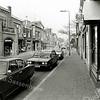 F1333a <br /> De Hoofdstraat, van zuid naar noord. Rechts de winkel van Cor Versluijs op Hoofdstraat 210.  Links het karakteristieke pand van H. J. Uphoff, waarvan de naam aangepast is door Cupido Boetiek die er toen een modewinkel had. De gevel is weer gerestaureerd en nu (2016) is Melman Lingerie er gevestigd. In ditzelfde jaar werd aan dit pand de Oud Sassenheim Restauratieprijs toegekend.