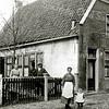 F2168<br /> Dit pand uit de 17de eeuw was gelegen aan de Hoofdstraat nr. 185 (oude telling, nu nr. 259) tegenover de Oude Haven. Het is een koffiehuis met een boerderij erachter (nr. 183); eigenaar was P. Ruijgrok. Deze verkocht het pand in 1920 aan G. Gardien en deze verkocht het in 1925 weer aan zijn schoonzoon W. van Hage. De laatste liet in hetzelfde jaar een grondige verbouwing uitvoeren door aannemer Kiebert. Vanaf toen was er sprake van Café Van Hage. In de loop der jaren heeft het café nog diverse veranderingen ondergaan. Nu (2017) is al sinds jaren groenteman P. van der Veer erin gevestigd. In het pand uiterst rechts is nu de winkel van Keurslager Scholten; op de foto is het nog een woonhuis. De personen op de foto zijn onbekend. Foto: ca. 1918.
