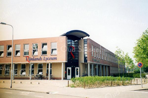 F0652 <br /> Het Rijnlands Lyceum aan de Van Alkemadelaan. Rechts de Kwekersweg. De school startte hier in 1972 met twee brugklassen havo/vwo.  In 1985 fuseerde de school met de Dr. De Visser-mavo. Het schoolgebouw op de foto is in 1995 in gebruik genomen en in 2007 werd de school uitgebreid wegens een gestaag groeiend leerlingenaantal. Er wordt les gegeven op mavo-, havo- en vwo-niveau. Anno 2016 telt de school bijna 1300 leerlingen. Foto: 2002.