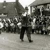 F2335<br /> Adest Musica in Sassenheim-noord. Voorop loopt tambour-maître Henk Hoogervorst, erachter o.a. gebroeders Van der Hulst..