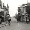 F4604<br /> De Hoofdstraat met links Café-Restaurant Het Bruine Paard en rechts op de hoek de winkel van De Haas. Foto: 1975.
