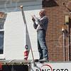 F4543<br /> Fotograaf Cees Turk. Hij staat op de luifel van zijn winkel aan de Hoofdstraat om op te fotograferen.