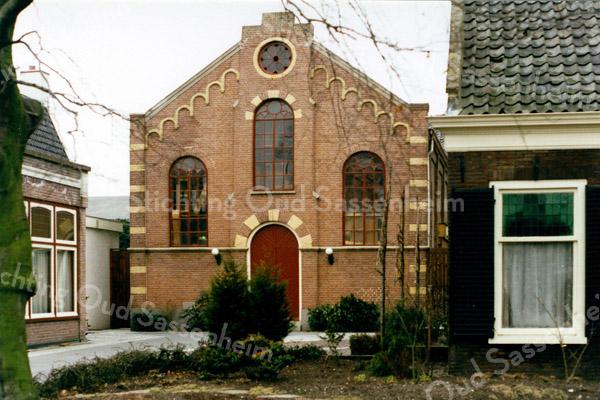 F0202b <br /> Voorzijde van de voormalige gereformeerde kerk uit 1876, gelegen aan de Hoofdstraat 137A. Links de voormalige pastorie (bouwjaar 1869) en rechts het voormalige kostershuis met kerkje, bouwjaar ca. 1820. Later was hier vele jaren de kruidenierswinkel van de dames Roosa. Voor een uitvoerige beschrijving zie het boekje van ds. R.J. Bakker Kistenmakerij in de kerk, uitgegeven door Kistenfabriek M. Bakker en Zn. in 1986. Foto: 1986.uitgegeven door Kistenfabriek M. Bakker en Zn in 1986. Foto: 1986.
