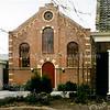 F0202b <br /> Voorzijde van de voormalige gereformeerde kerk uit 1876, gelegen aan de Hoofdstraat 137A. Links de voormalige pastorie (bouwjaar 1869) en rechts het voormalige kostershuis met kerkje, bouwjaar ca. 1820. Later was hier vele jaren de kruidenierswinkel van de dames Rooza (later ook Roosa). Voor een uitvoerige beschrijving zie het boekje van ds. R.J. Bakker Kistenmakerij in de kerk, uitgegeven door Kistenfabriek M. Bakker en Zn. in 1986. Foto: 1986.uitgegeven door Kistenfabriek M. Bakker en Zn in 1986. Foto: 1986.
