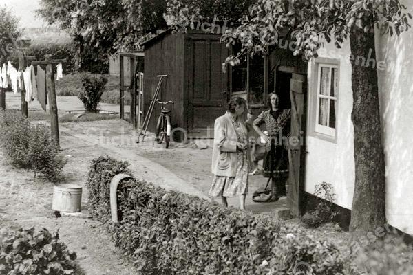 F1867 <br /> Een gezellig buurpraatje aan de Teylingerlaan bij de ruïne. In de deuropening staat mevr. van Klaveren. Foto: ca. 1948.