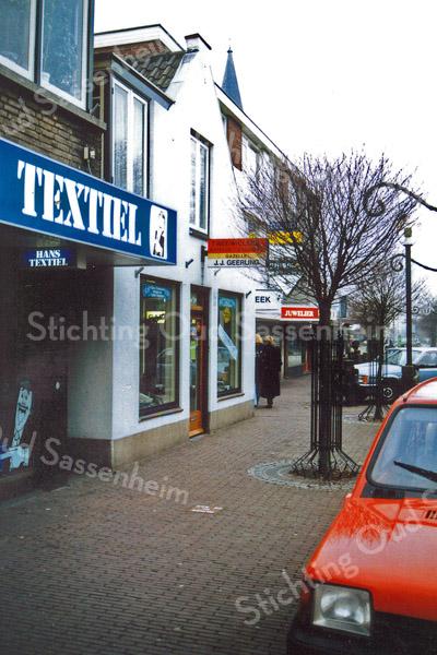 F0247 <br /> Een foto van verschillende winkels in het centrum van Sassenheim. De winkel van Hans Textiel op de voorgrond (nu in 2016 Holtman dierenspeciaalzaak), daarnaast de rijwielhandel van J.J. Geerling. Die zaak is eind jaren '80 opgeheven. Nu (2016) is de brillenspecialist Clair Optiek daar gevestigd. Verderop het uithangbord van de apotheek. Daarboven de torenspits van de r.-k. kerk St. Pancratius. Foto: eind jaren '80.