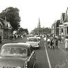 F1010 <br /> Een rij auto's met gasten op de Hoofdstraat ter gelegenheid van de priesterwijding van C.J. van der Voort op 31-5-1958.