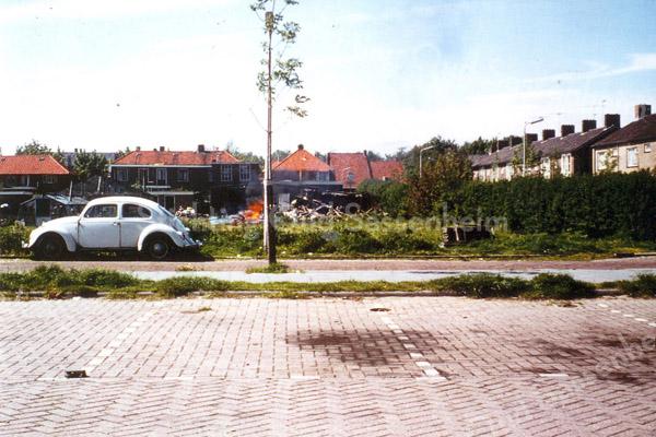 F0267 <br /> Geheel rechts de Essenlaan in de jaren '70. Op de voorgrond het parkeerterrein van garage Van den Dool. Waar de auto staat, is nu de Venusstraat, tevens toerit naar de Apollostraat, die in 1977 is gebouwd. Op de achtergrond de huizen aan de Rusthofflaan van achteren gezien en de bollenschuur van Roozen. Rechts naast het boompje het huis van Beijk sr. (zie F0260). Rechts daarvan café Sportrust met woonhuis, afgebrand in 1979 (zie foto F0258).  Foto: ca 1975.