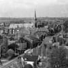 F4027 <br /> Een foto genomen vanuit de toren van de r.-k. kerk St.Pancratius. Links huize West End nog in volle glorie; het St. Annaklooster en het huis van de fam. v.d. Voort. Dan de huizen langs de Charbonlaan en het dak van de Herv. School. In het midden het dak van het KSA-gebouw en het postkantoor. Vooraan rechts het witte huis van de fam. Tijssen; het huis van wed. de Groot en het pand van IJsselmuiden. Foto: 1951