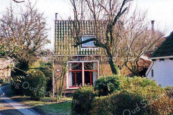 F0147 <br /> Hoofdstraat 102, het voormalige huis van de fam. Drost (de bekende melkboer). Het huis is gebouwd ca. 1834 en is inmiddels geheel gerestaureerd. Het wordt bewoond door mr. J.W. Janssen. De foto is genomen vanaf de Hoofdstraat en laat slechts de smalle kant van het huis zien. Het pand ligt een eindje van de weg af, vlak achter het bekende witte huisje op nr. 100.