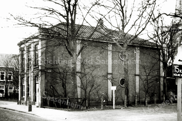 F0290 <br /> Het woonhuis van het hoofd van de hervormde school, A. den Haan aan de Hoofdstraat. Het is niet bekend, wanneer het huis is gebouwd, waarschijnlijk in 1866 tegelijk met het verenigingsgebouw (toen openbare school). Het was voor die tijd een riante woning, gelegen naast de ingang van de Ned.-herv. kerk en naast de school. Rechts de toren van de  Ned.-herv. Kerk of Dorpskerk. Links van de fietser is de winkel van Jan v.d. Klugt op de achtergrond te zien. Foto: vóór 1967.