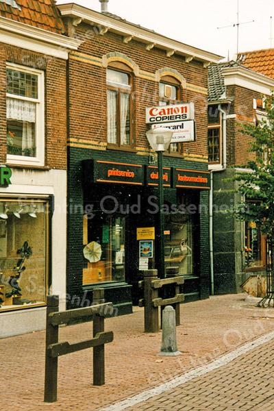F2002<br /> De Hoofdstraat met het pand van Multicopy, voorheen van Cor Versluijs. Links van het pand de schoenenwinkel van Brouwer.
