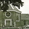 F3209<br /> De Ned. Herv. kerk of Dorpskerk. Deze kerk, gewijd aan de heilige Pancratius wordt het eerst vermeld in een oorkonde uit 739, waarin Willebrordus zijn bezittingen vermaakt aan de Abdij van Echternach. Het tufstenen gedeelte stamt uit de 12de eeuw. Tijdens ds. Kloppenburg werd de kerk vergroot en door de aanbouw van het lagere gedeelte kreeg de kerk het tegenwoordige aanzien. In 1923 werd het interieur verbouwd, de kansel werd vanuit het koor naar de torenkant (onder het orgel) verplaatst. Het portaal aan de kant van de Hoofdstraat werd weggebroken en de ingang werd verplaatstnaar het koor.