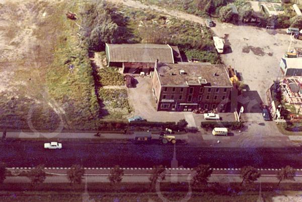 F4318<br /> Een luchtfoto van de bollenschuur van W.J. Eldering & Zn aan de Rijksstraatweg 59. Rechts staat de koffietent 'De Uiver' van H. van Zoen. Daarachter het parkeerterrein en de oprit naar de houtopslag van De Regt.