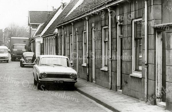 F0936 <br /> De Kerklaan, gezien vanaf de Hoofdstraat. Op de voorgrond de diaconiehuisjes van de Ned.-herv. kerk. In het eerste huis woonde eertijds Gerrit de Bruijn met zijn zuster. Dan de huizen waar Jo van Waardenburg en mevr. Schalk woonden. Verder het witte pand van G. van Egmond en daarna weer huizen van de diaconie. Het hoge pand was de olieschuur van Jac. Oudshoorn.  In de jaren '60 was de voormalige olieschuur van Jac. Oudshoorn in gebruik als opslagruimte van de aardewerkfabriek. Foto: jaren '60.