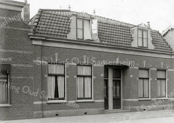 F0818 <br /> Naast het pand van A. van Breda, nog net zichtbaar op de foto, werd in 1901 dit pand van twee woningen aan de Hoofdstraat gebouwd. Ook dat is bewaard gebleven. Naast het rechterpand ligt de Burchtstraat. Foto: vóór 1921.<br /> <br /> Collectie Oudshoorn 022: twee woonhuizen J.P. Oudshoorn 1901, Hoofdstraat 215 en 217 volgens de oude nummering, nu nummers 293 en 295.