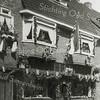 F2786<br /> De feestelijk versierde kruidenierswinkel van Cor van Goeverden aan de Hoofdstraat 207. Hij kreeg de 1ste prijs op het bevrijdingsfeest van 31 augustus 1945.<br /> De kruidenierswinkel is later overgenomen door zoons Cor en Jacques. In 1961 verbouwd tot zelfbedieningswinkel. In 1986 zijn zij gestopt met de zaak en is het bedrijf overgenomen door de fa. de Jong die er lederwaren ging verkopen. Nu is het een winkel voor boeken en kantoorbenodigdheden.