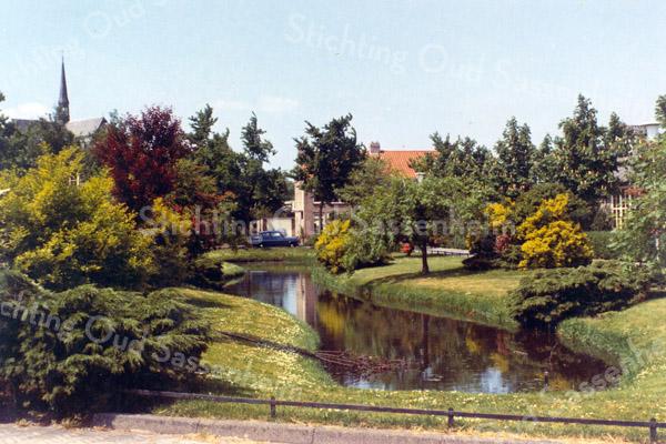 F0642 <br /> Waterpartij aan de Dr. de Visserlaan met links een gedeelte van de St. Pancratiuskerk. In het midden de huizen langs de St. Antoniuslaan. Rechts is een glimp te zien van het voormalige schoolgebouw.