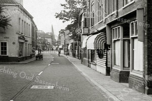 F0973 <br /> Hoofdstraat, gezien vanuit noordelijke richting. Het witte pand aan de linkerkant was destijds de winkel van Bemelman. Nu (2016) is hier café De Twee Wezen gevestigd. Geheel rechts op de foto de kruidenierszaak van  Van Nieuwkoop; nu is daar restaurant Op eigen Wijze  gevestigd. Daarnaast het pand van J. van Nieuwkoop, nu cadeau-  en kookwinkel Van Nieuwkoop. Achter de tweede markies is slagerij Scholten en daar weer achter café Van hage. Foto: ca. 1951.