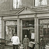 F2079<br /> Maarten van Hage (Lisse 25-5-1876; Sassenheim 10-2-1948) voor zijn slagerswinkel, Hoofdstraat 172. De winkel stond op de plek waar later de schoenenwinkel van Aart Witte is gebouwd (thans Van der Riet). Maarten trouwde tweemaal: eerst met Maria Jacoba Bergman (overl.19-12-1918) en later met Christina Hulsbosch.