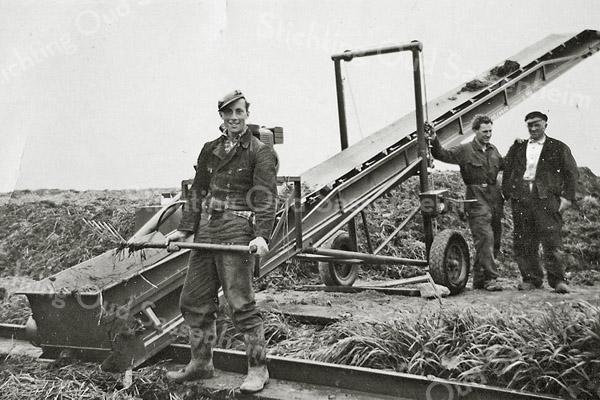 F3087<br /> Rechts staat Bram Molenaar met naast hem een knecht. Vooraan staat zijn zoon Cees Molenaar bij een transportband om de schuiten vol te laden.