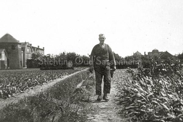 F1424 <br /> De heer G. van der Voort in het bollenland van Papendrecht. Links de molen van Speelman en de bollenschuren van C.J. Speelman & Zonen. Rechts huize St. Bernardus. Nu is hier de Koetsiersweg.